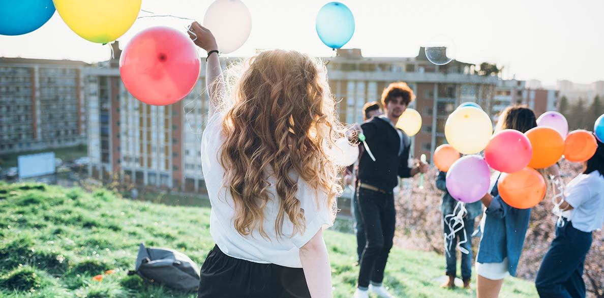 a girl holding coloured balloons at the party