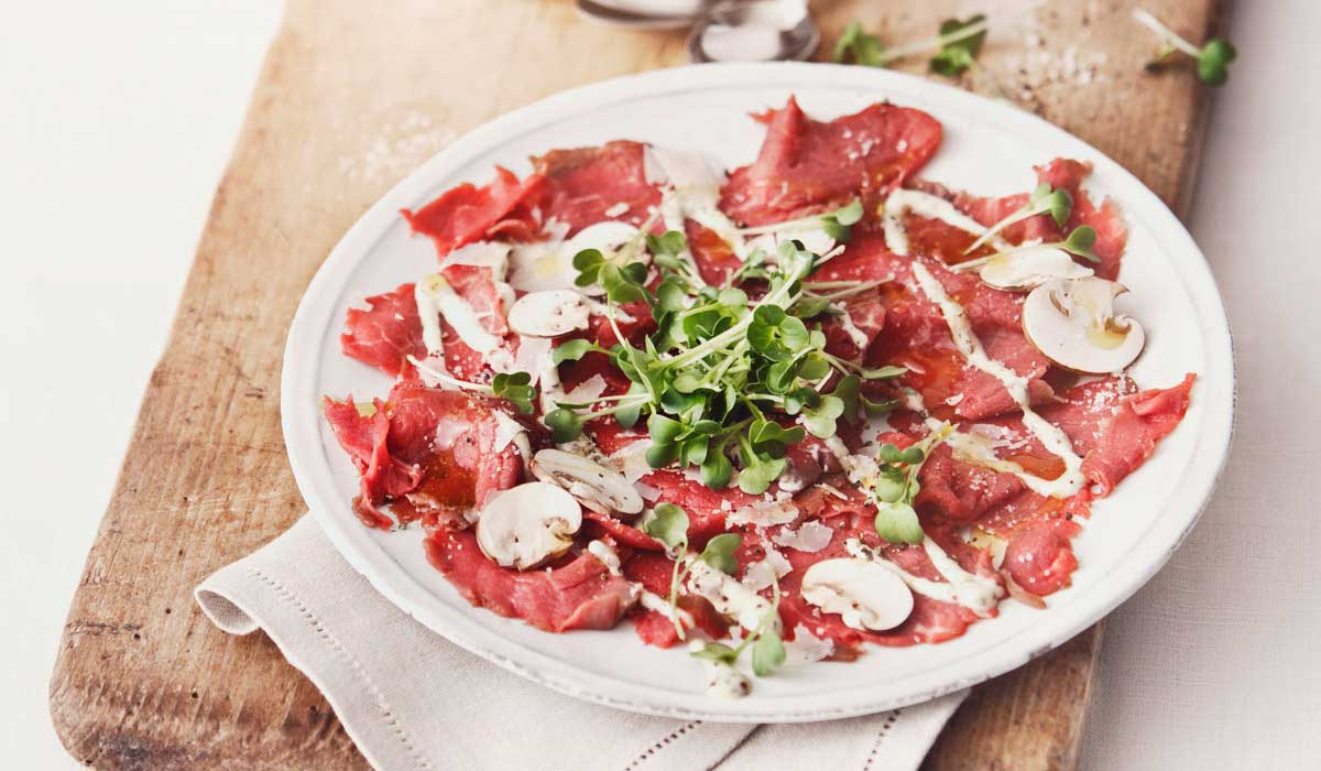 plate of sliced beef carpaccio topped with microgreens and drizzled with sauce