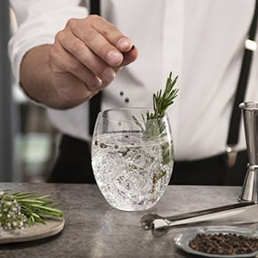 glass of san pellegrino tonic water with rosemary and peppercorns