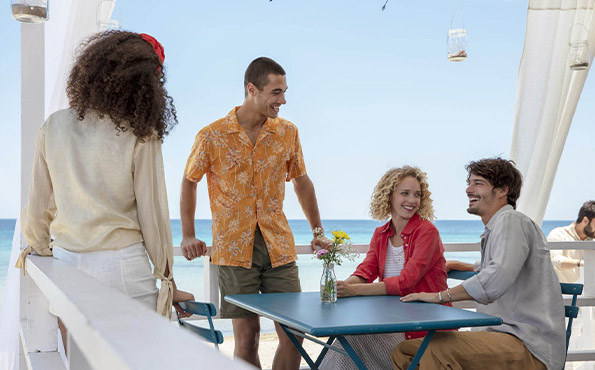 Friends relax together at a bar table near the beach