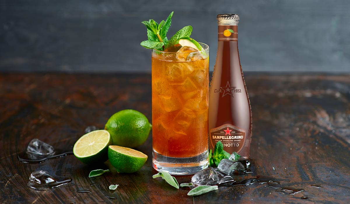 highball glass of green chinotto mocktail over ice garnished lime wedges and mint next to san pellegrino chinotto bottle
