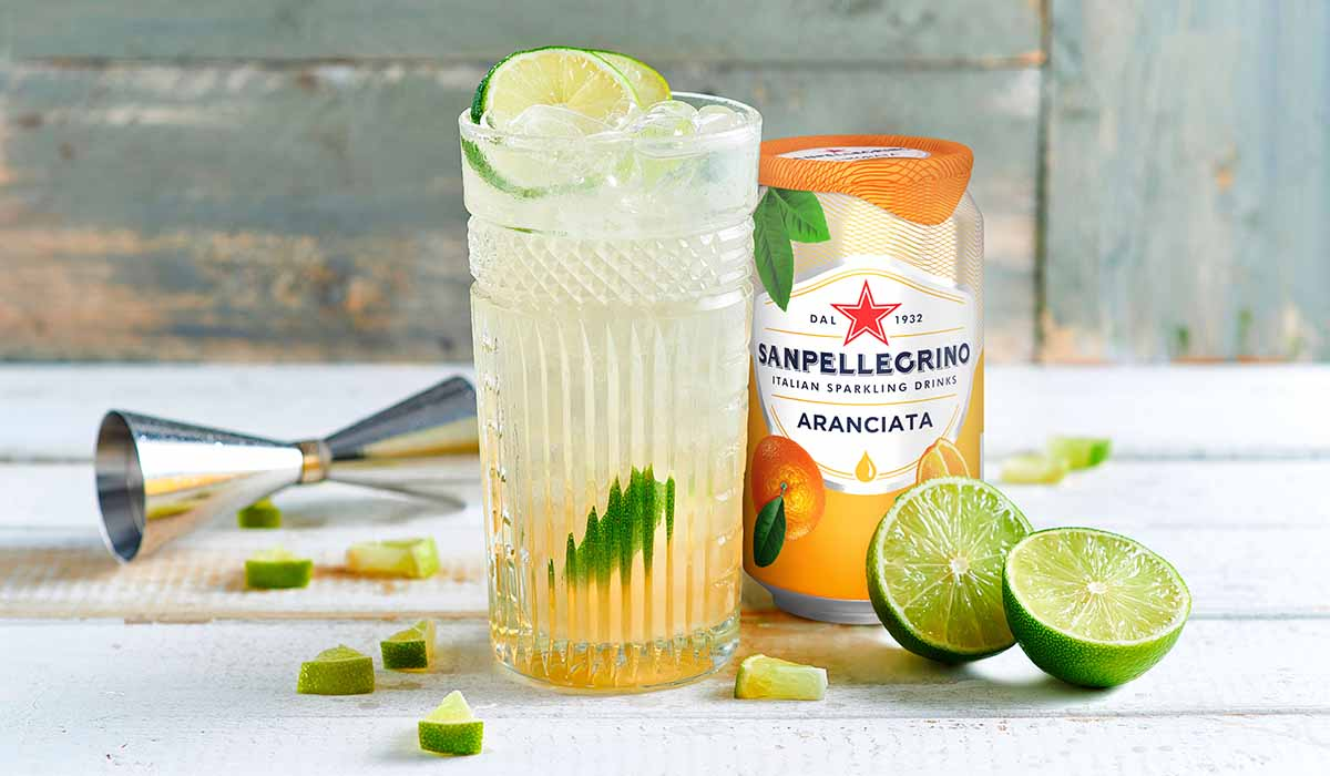 glass of after orange mocktail drink over ice with can of aranciata and lime wedges
