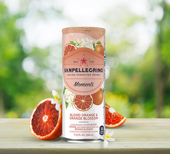 Can of Sanpellegrino Momenti Blood Orange & Orange Blossom on a table with fresh blood oranges slices