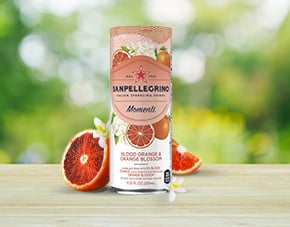 Can of Sanpellegrino Momenti Blood Orange e Orange Blossom on a table with fresh blood oranges slices