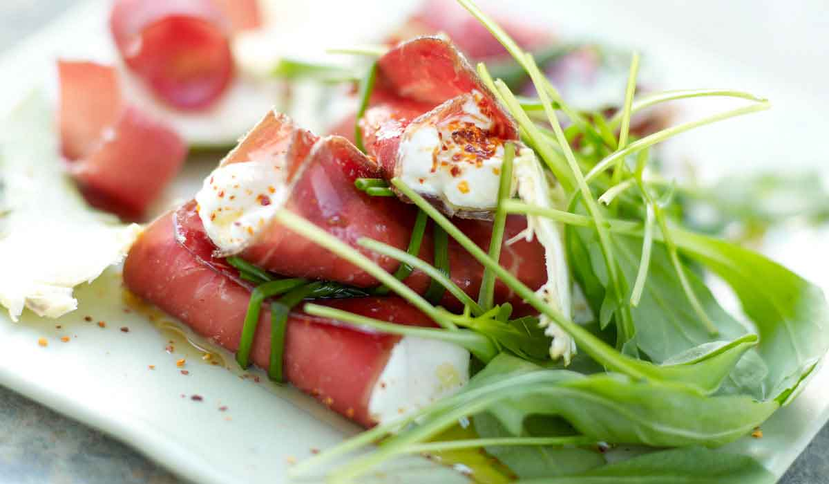 bresaola goat cheese roll ups with arugula on a plate