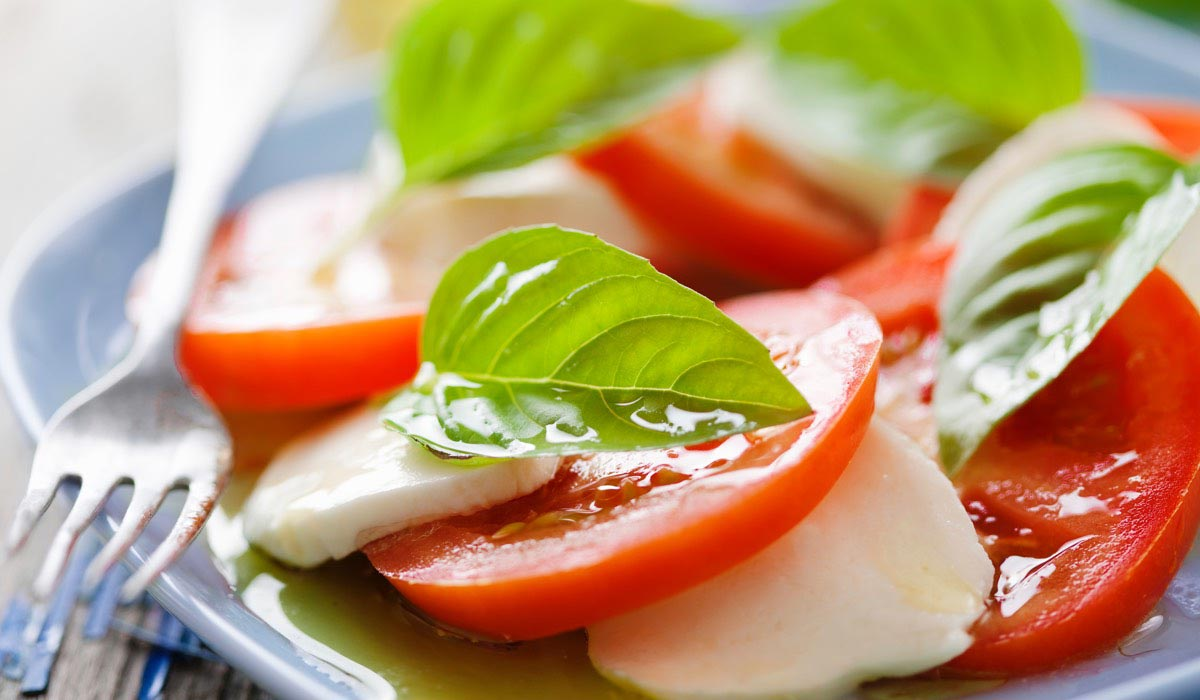 tomatoes, mozzarella and fresh basil on a plate